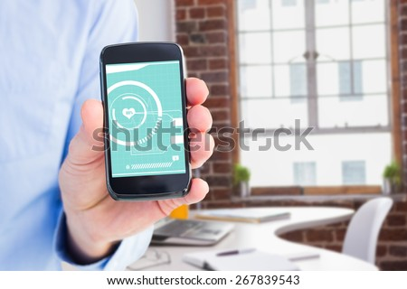 Businessman showing his smartphone to camera against laptop on desk with glasses and notepad - stock photo