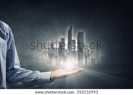 Businessman showing in palm glowing modern city model - stock photo