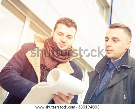 businessman showing notes at office building exterior - stock photo
