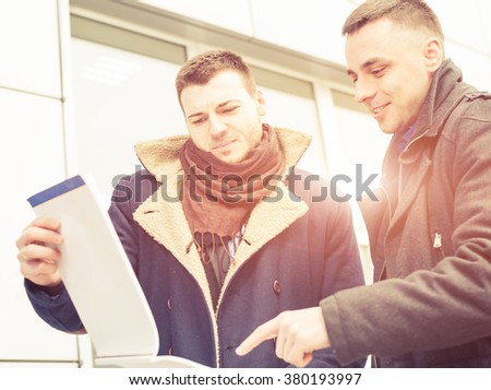 businessman showing notes to a partner outside - stock photo