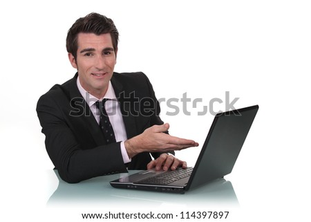 Businessman showing off his new laptop - stock photo