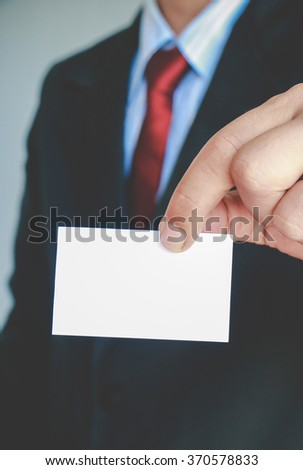 Businessman showing paper on gray background,Vintage tone style. - stock photo