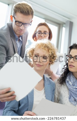 Businessman showing photograph to colleagues in creative focus - stock photo
