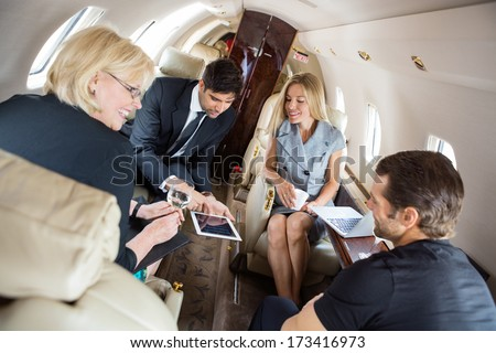 Businessman showing presentation on digital tablet with colleagues in corporate jet - stock photo