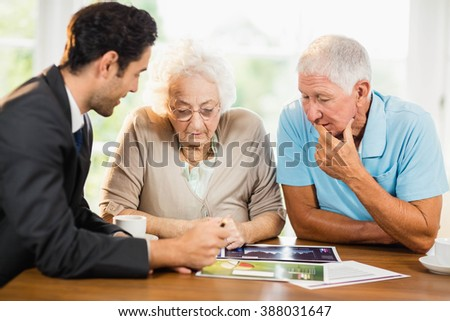 Businessman showing sheets to senior couple at home - stock photo