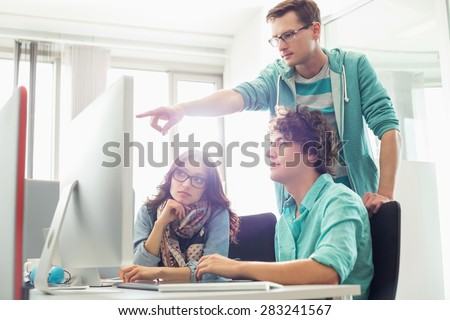 Businessman showing something to colleagues on computer in creative office - stock photo