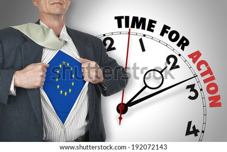 Businessman showing superhero suit with flag from Europe underneath his shirt standing against clock with time for action - path for the shirt - stock photo