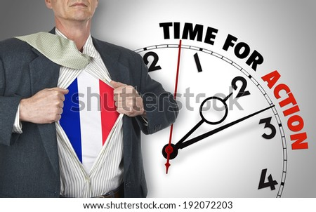 Businessman showing superhero suit with flag from French underneath his shirt standing against clock with time for action - path for the shirt - stock photo