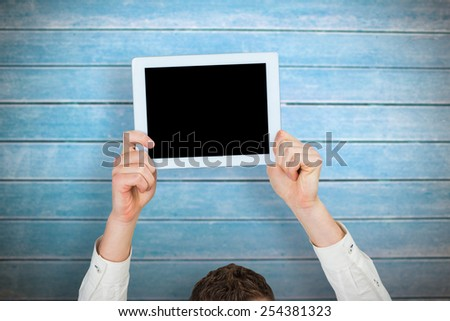 Businessman showing tablet above head against wooden planks - stock photo