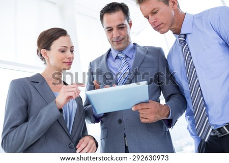 Businessman showing tablet to his colleagues in the office - stock photo