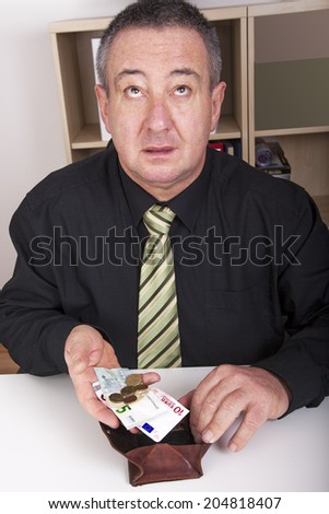Businessman showing the meager contents of his wallet - stock photo