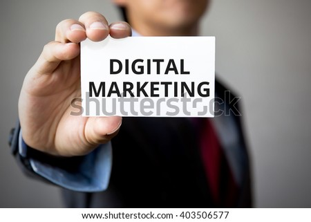 Businessman showing the text 'Digital Marketing' on white card - stock photo