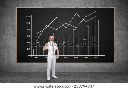 businessman showing thumb up and drawing chart on blackboard - stock photo