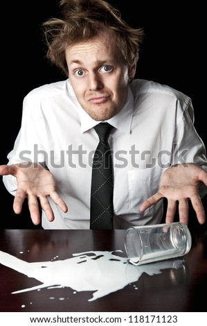 Businessman shrugs and helpless after knocking over glass of milk on table, desaturated with black background - stock photo