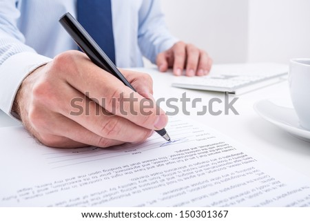 Businessman signing a document. - stock photo