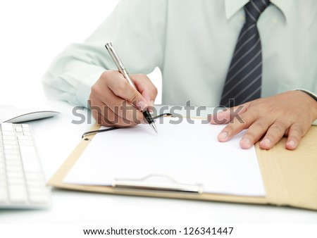 Businessman signing a document on the desk - stock photo