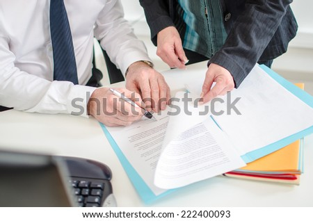 Businessman signing a documents presented by his secretary at the office - stock photo