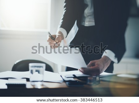 Businessman signing documents at desk in office wearing black suite and white shirt, close-up of male hands holding contract, filtered image, flare light - stock photo