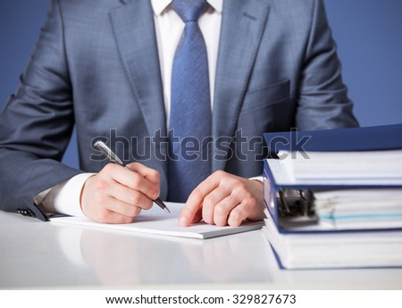 Businessman signing documents, blue background - stock photo