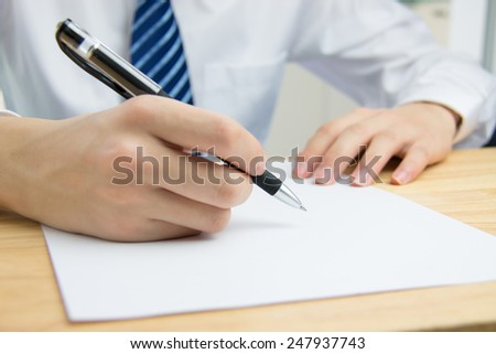 Businessman signing documents in the office - stock photo