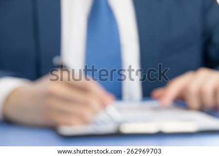 businessman signing documents to businessman in blur background - stock photo