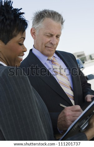 Businessman signing documents while standing with business woman - stock photo