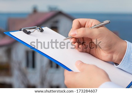 businessman signs a document on the background of an apartment building with blue sky - stock photo