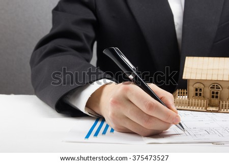 Businessman signs contract behind home architectural model - stock photo