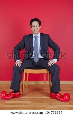 Businessman sited next to a red wall with clown shoes - stock photo