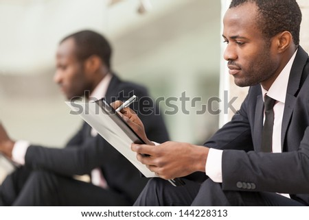 Businessman sits and work with document - stock photo