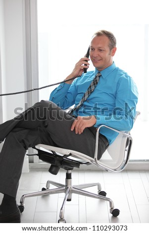 Businessman sitting and talking on the phone - stock photo