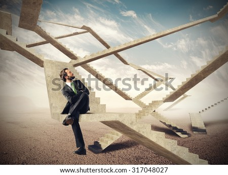 Businessman sitting and watching the endless stairs - stock photo