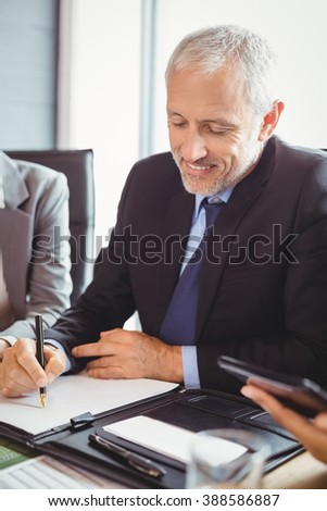 Businessman sitting and writing a report in conference room - stock photo