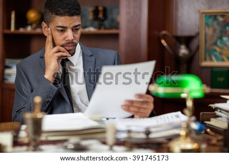 businessman sitting at a table in the office and i read an important document - stock photo
