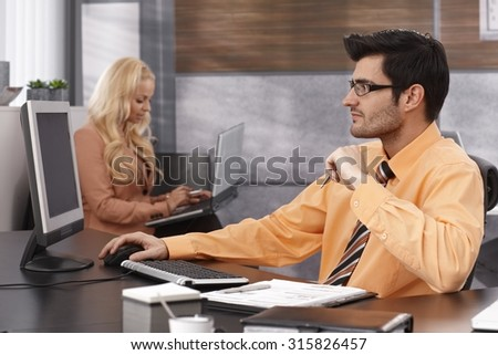 Businessman sitting at desk in office, working with computer. - stock photo