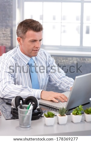 Businessman sitting at desk, using laptop computer, working. - stock photo