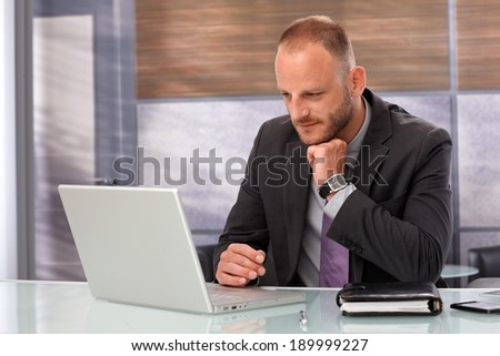 Businessman sitting at desk, working with laptop computer in office. - stock photo