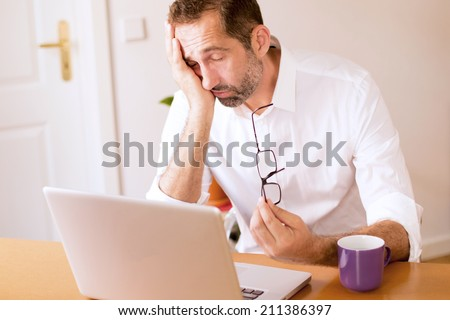 businessman sitting at his desk and falling asleep - stock photo