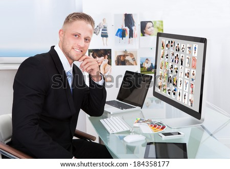 Businessman sitting at his desk in front of a large screen monitor editing photographs - stock photo