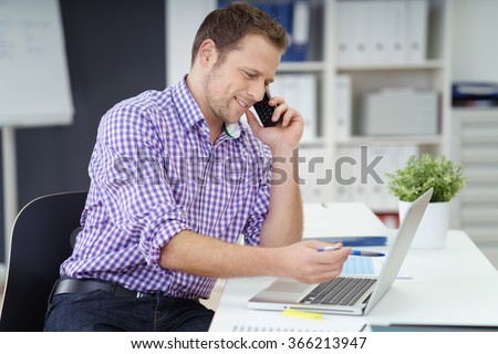Businessman sitting at his desk in the office checking something on his laptop computer as he chats on the phone with a smile - stock photo