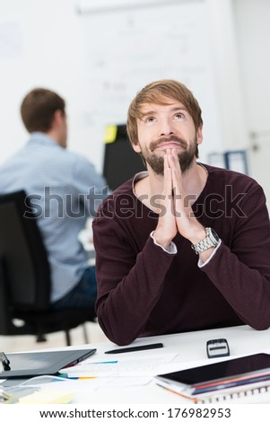 Businessman sitting at his desk in the office offering up a prayer for success with a wry smile on his face - stock photo