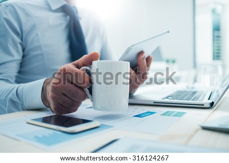 Businessman sitting at office desk having a coffee break, he is holding a mug and a digital tablet - stock photo