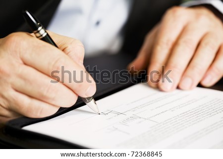 Businessman sitting at office desk signing a contract with shallow focus on signature. - stock photo