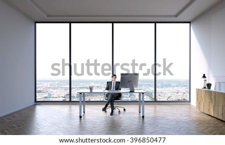 Businessman sitting at table in big office. Panoramic window behind. City view. Concept of work. - stock photo