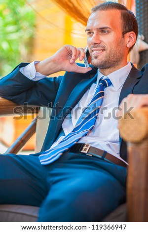 Businessman sitting at table in cafe using laptop computer, talking on mobile. - stock photo