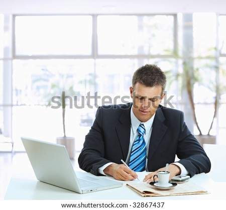 Businessman sitting at table in office lobby, writing note on paper. - stock photo