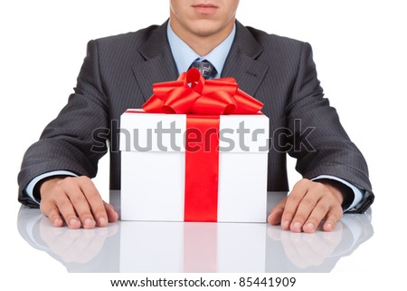 Businessman sitting at the desk with gift box isolated over white background, series photo - stock photo