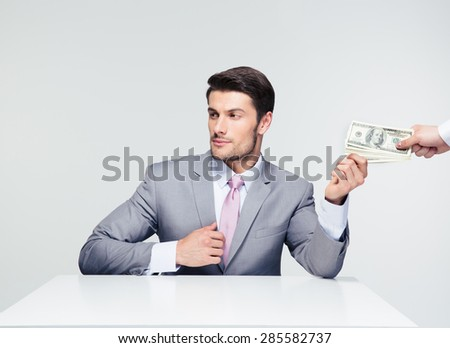 Businessman sitting at the table and taking bribe over gray background. Looking away - stock photo