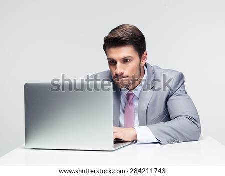 Businessman sitting at the table and working on the laptop  over gray background - stock photo