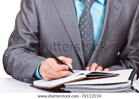 Businessman sitting at the table and working with documents, sign up contract, writing something in his notebook, notepad. Isolated on white background - stock photo